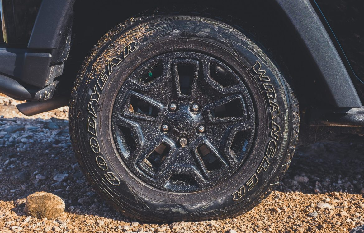 A close-up of a vehicle with flat tire on a dirt road.