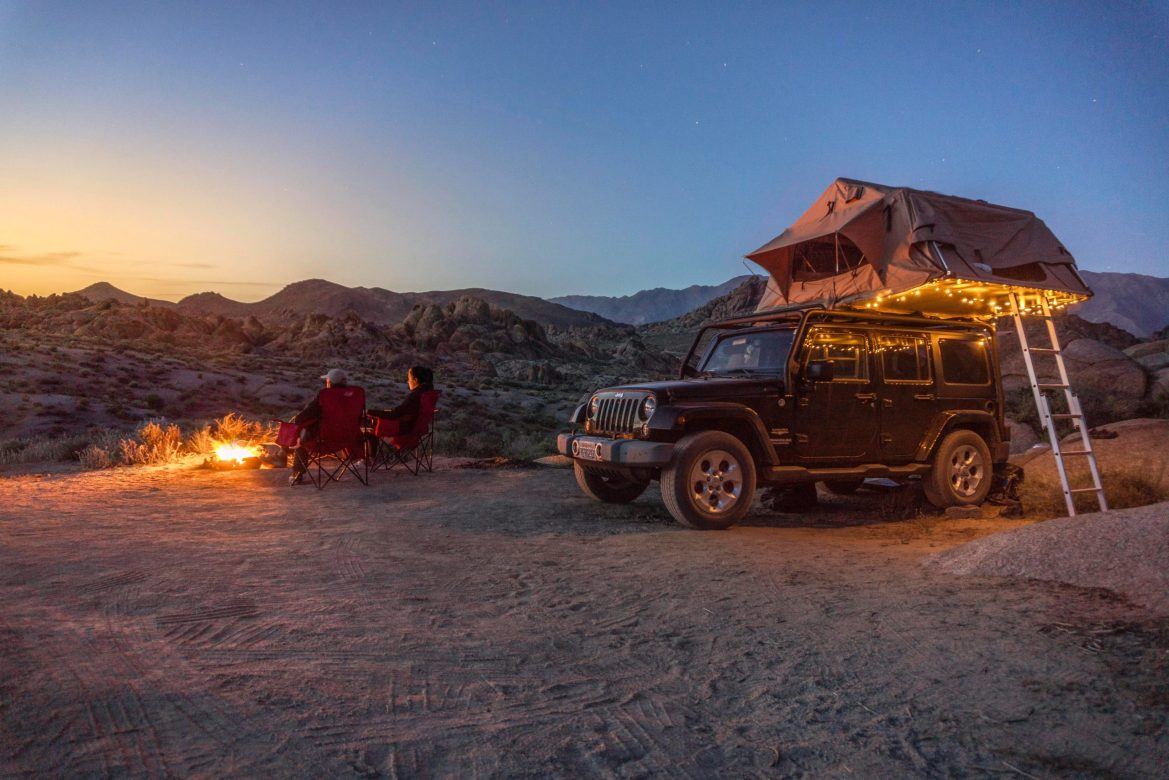 A jeep with a roof tent is parked in the desert. Off to the side, two people sit in camp chairs around a fire, gazing at the sun setting behind the mountains in the distance.