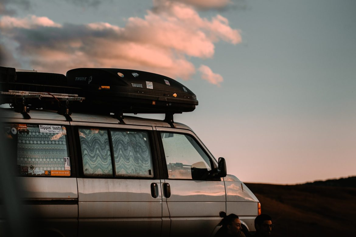 Two people sit outside a van parked at sunset.