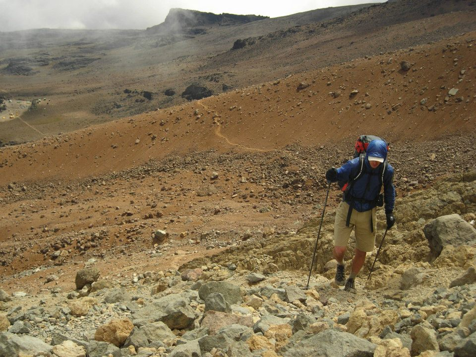 Lichter backpacks up a barren climb in Africa. He wears a jacket, gloves, and a brimmed hat.