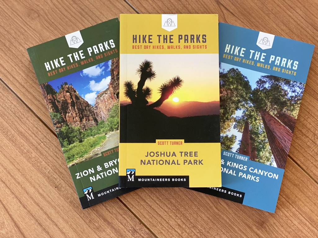 Three of Scott's national parks guidebooks lie on the floor: Zion and Bryce; Joshua Tree; and Sequoia and Kinds Canyon.