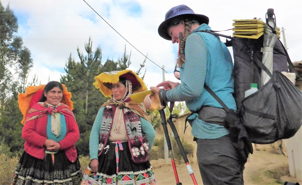Fidgit, laded down with her backpacking gear, interviews two Quechua women.