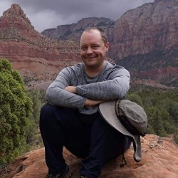 Scott Turner smiles for the camera while sitting on a rock with his arms crossed on his knees. Red and gold canyons loom in the background.