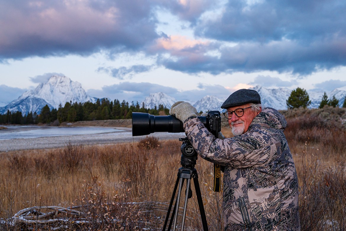 Tom Mangelsen looks towards the camera as he sits in a field with his long-lens camera set up on a tripod. Snowy Tetons loom into the cloudy sky in the distance.