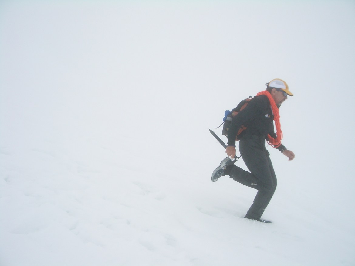 Buzz runs down a snow slope in a white-out. He's carrying an ice ax, shouldering a cord of rope, and wearing a backpack.