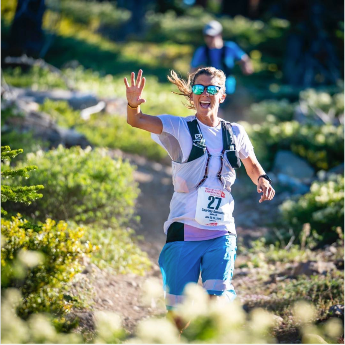 Courtney smiles and waves as she runs down a lush trail near Lake Tahoe during the Western States 100 Endurance Run. She's wearing long blue shorts, a white t shirt, reflective sunglasses, and a hydration pack.