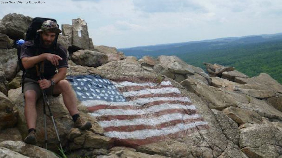 Sean Gobin sits on a rock painted with an American Flag. He's wearing his backpacking pack and holding poles.