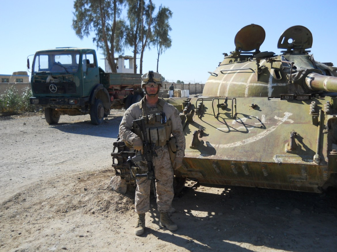 Sean Gobin stands in full combat gear in front of a military tank in the desert of south west Afghanistan.