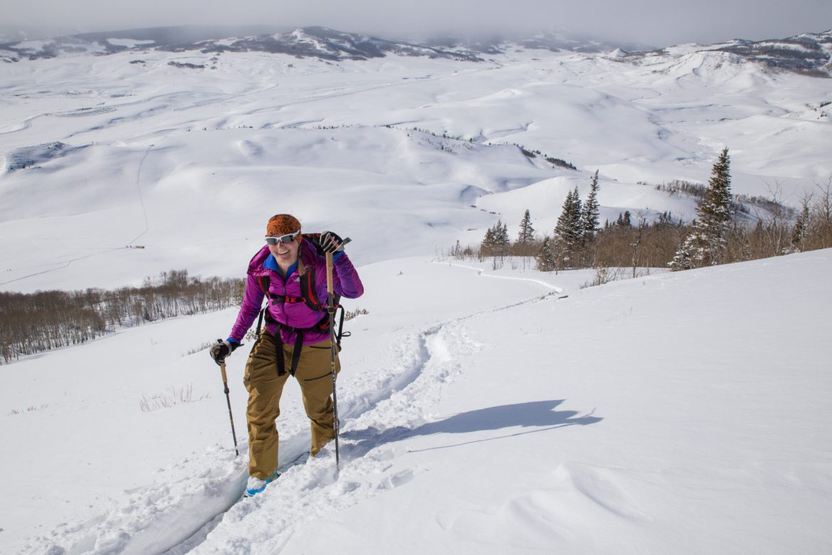 A backcountry skier skins up a track. Snow-covered plains sprawl out behind her.