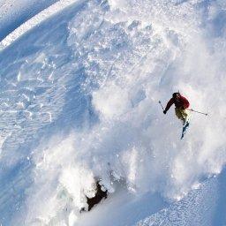 A skier flies through the air as snow shoots down the mountain below.