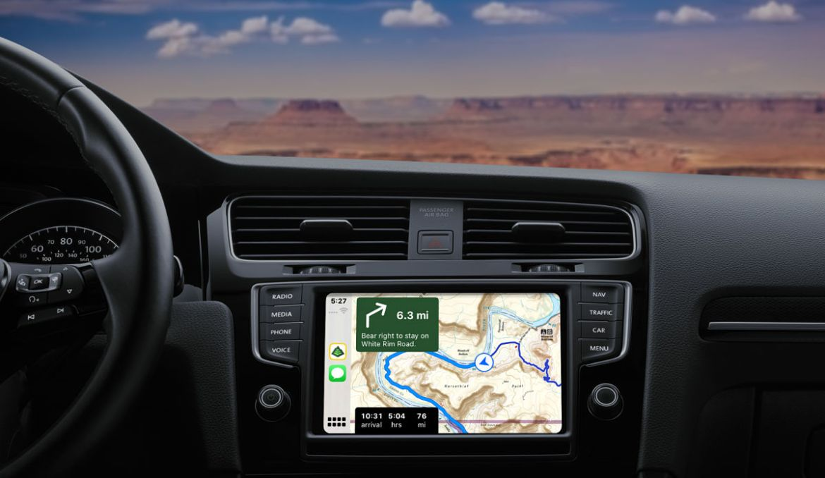 A car dashboard with Gaia GPS on Apple CarPlay shows turn-by-turn directions.