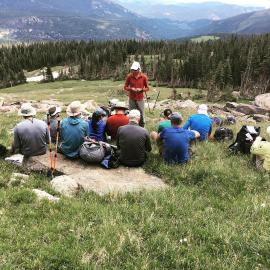 Andrew Skurka teaches backcountry navigation with map and compass in Rocky Mountain national Park. He stands in a meadow facing a group of people sitting on the ground.