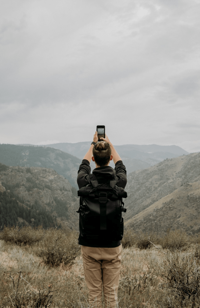 person holding there arms up to take a phone picture of a mountain range