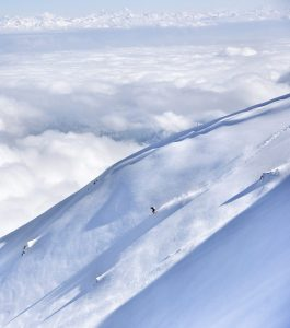 Smithwick skis down a giant Himalayan slope with clouds and tall snowcapped peaks in the distance.