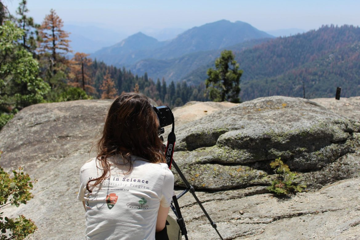 A GYF intern looks through a camera set up on a tripod. She's sitting on a rocky outcropping, gazing at mountains before her.