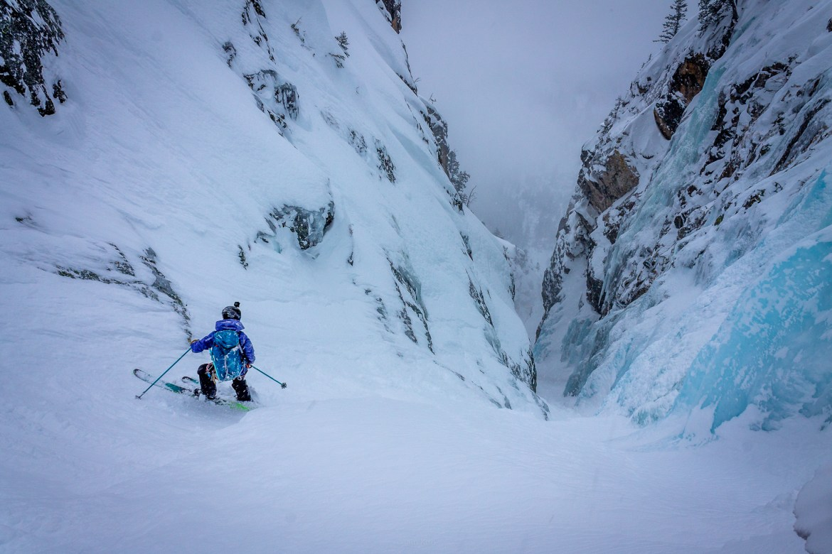 A skier stands at the top of a narrow, steep couloir with vibrant blue ice pouring in from the sides.