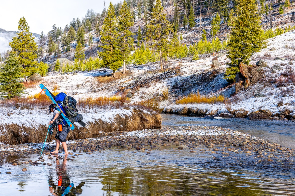 A person walks barefoot across a stream with skis and a big pack on their back. They're wearing a t-shirt and shorts, and carrying poles.