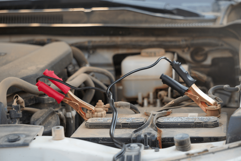 Air compressor cables hooked up to the battery of a car
