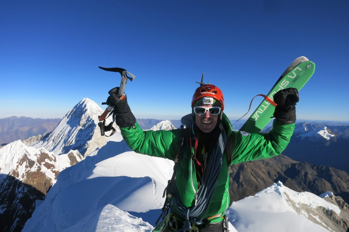 Adrian stands on top of a mountain holding an ice axe in one hand and his gloved fist raised in the other. His skis are on his back. He's wearing sunglasses, a headlamp, and a helmet. Snowcapped speaks are all around him in the background.