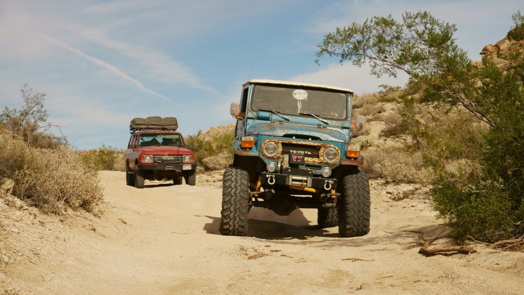 Old blue offroad vehicle followed by a read vehicle drive through the sand.