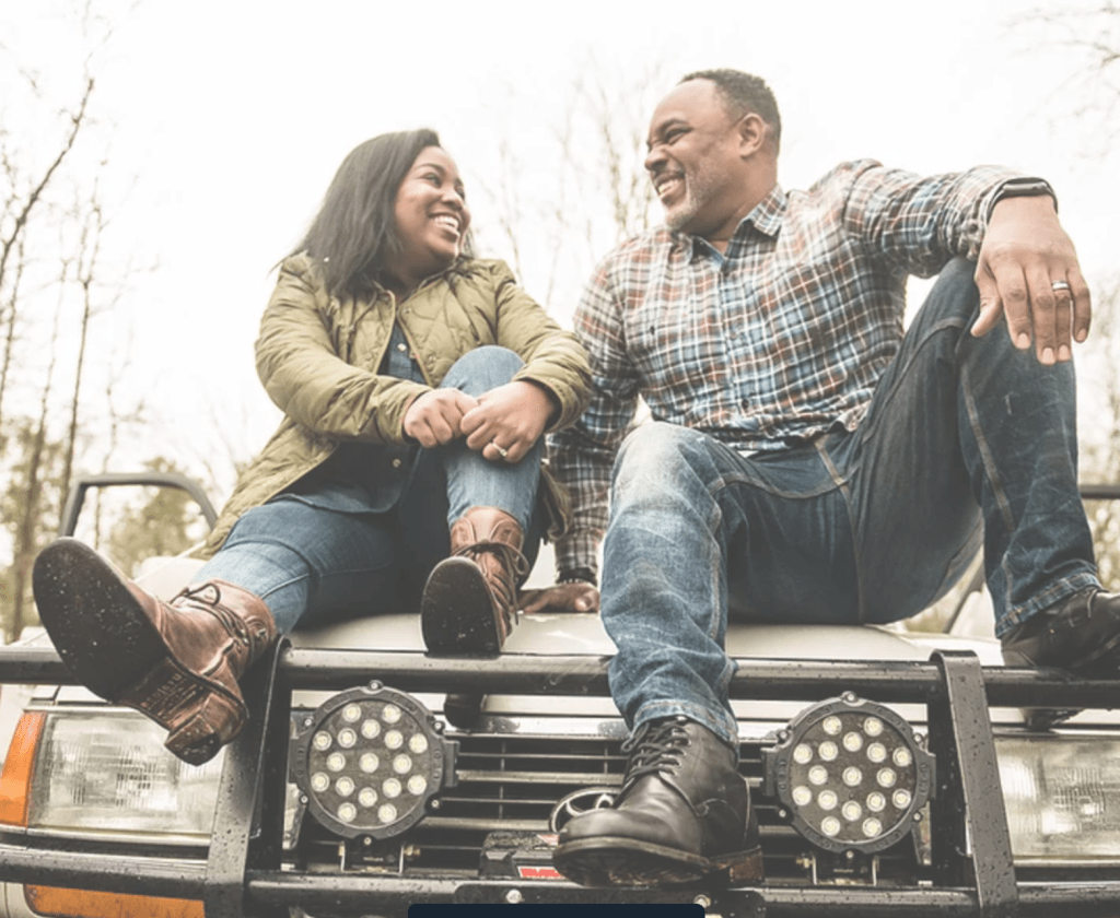 A man and a woman are sitting on the hood of their truck, smiling and looking at each other with love.