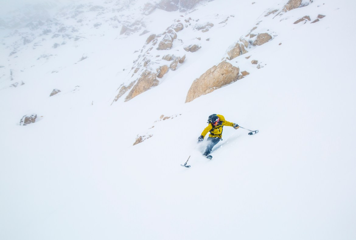 A skier with a leg difference sends it down a mountain. He is using outrigers and one ski.