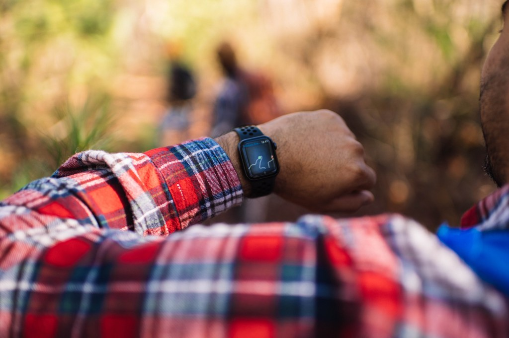 Person in red flannel holds up Apple Watch with Gaia GPS displaying position on watch route.