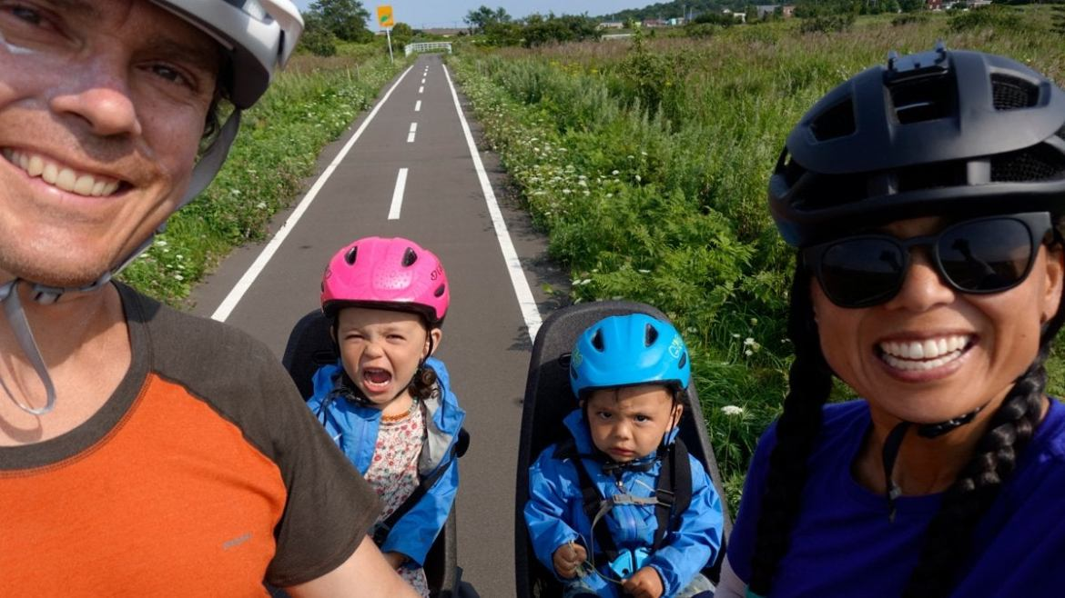 Jenny and Scott Jurek and their two kids smile for the camera on their bikes on a bike path in Japan.