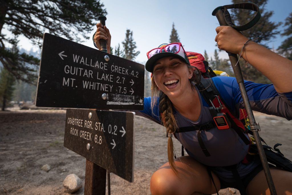 Allison smiles next to a trail sign on the JMT.