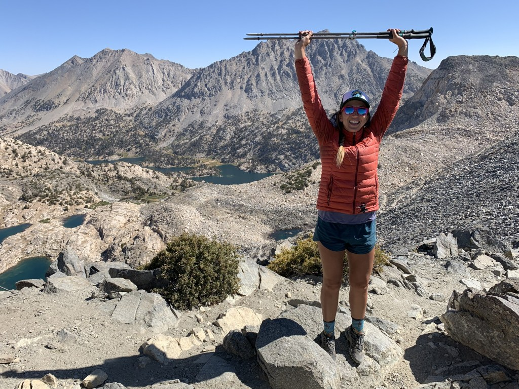 Allison smiles on the trail while holding her hiking poles over her head.