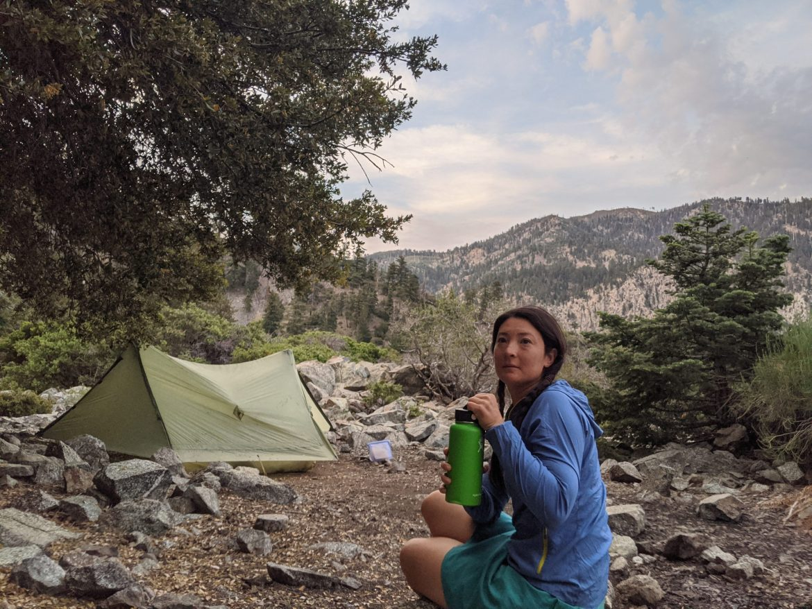 Liz Thomas sits with an insulated thermos in front of her tent.