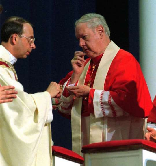 Cardinal Edward Michael Egan receives communion from his succesor Bishop William E. Lori during Lori's installation as the fourth Bishop of Bridgeport in 2001.