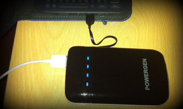 PowerGen Juice Pack with a Kindle plugged in to its integral micro-USB and an iPhone cable to one USB port
