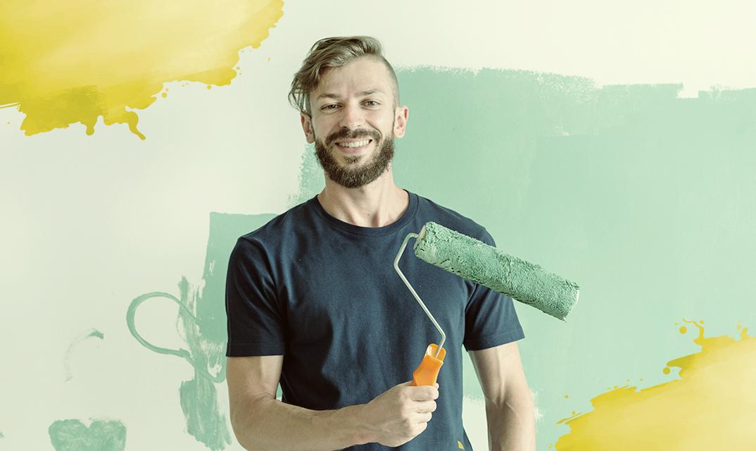 Homem jovem segurando um rolo de pintura.