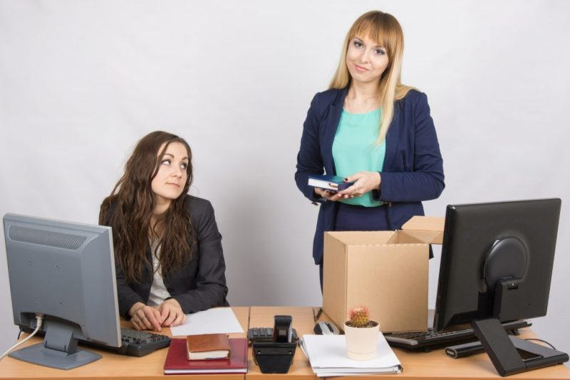 Girl in office standing with a smile in front of a box about colleagues