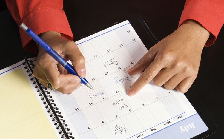 hands writing in a date-planner book