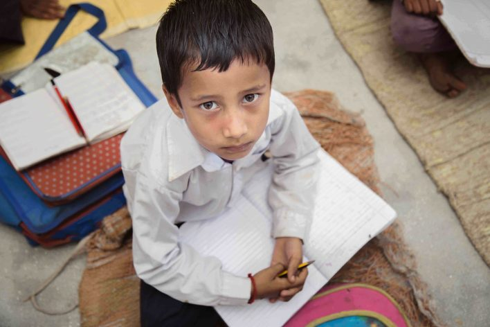 Child studying in a poor distant village