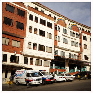 A view from the entrance of Hospital Arco Iris, including the hospital's two ambulances parked outside the Emergency Department