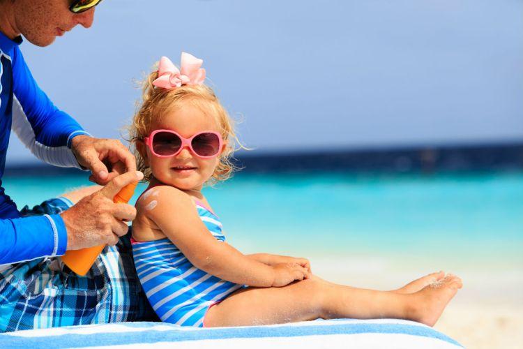 pai passando protetor solar na filha