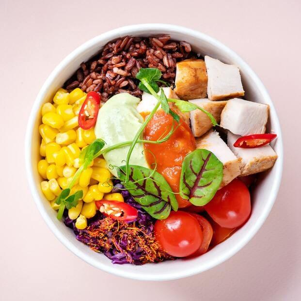 Poke a domicilio compuesto por maíz, arroz integral, pollo y tomates cherry