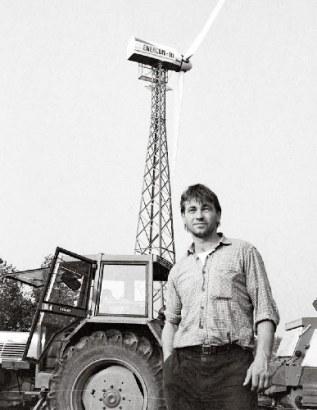 Ganz vorne dabei: Thomas Scharmer 1988 auf seinem biodynamischen Hof Dannwisch bei Hamburg vor einem der ersten Windräder der Republik, finanziert durch die GLS Bank.