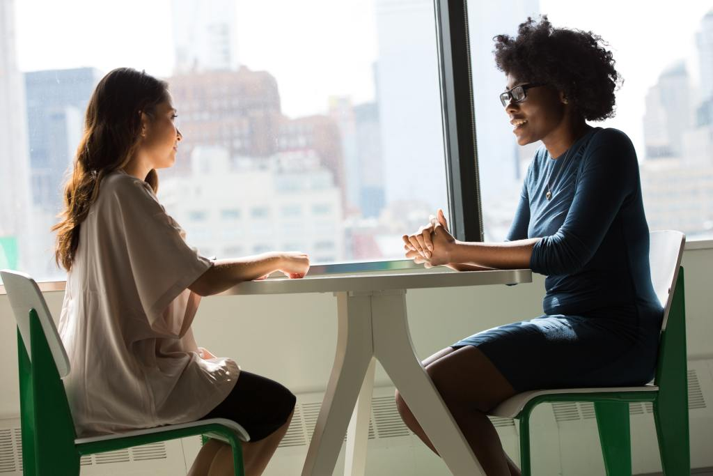 Two women sitting at a table for an interview