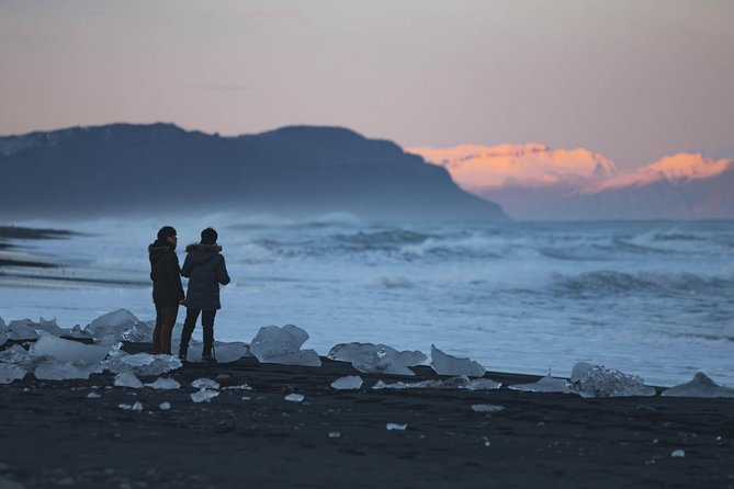 Two people standing on diamond beach at the glacier lagoon.