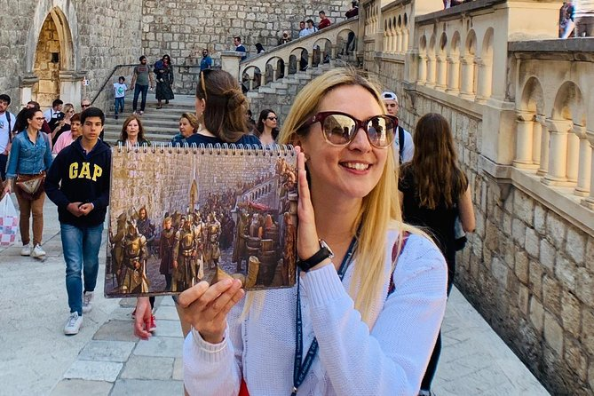 Woman holding up picture of scene from Game of Thrones. A Game of Thrones tour is one of the best things to do in Dubrovnik.