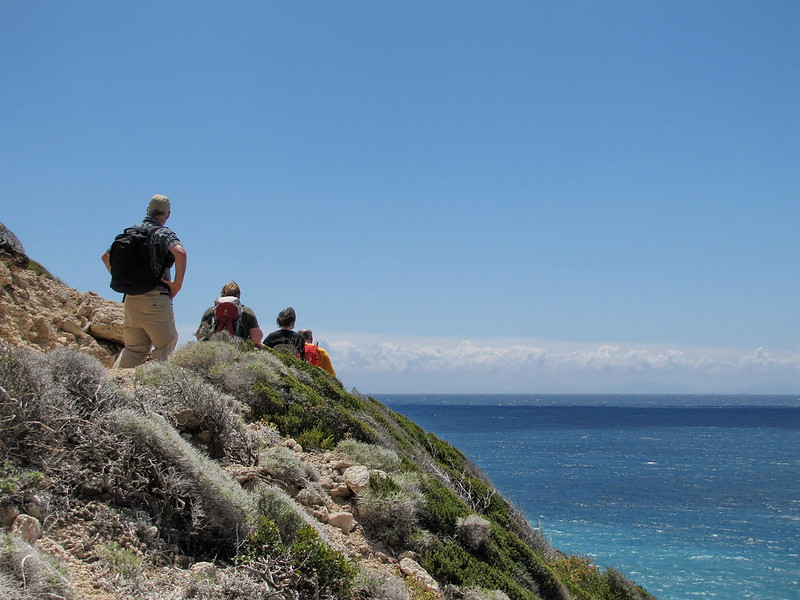 A group of people hiking along the coast in Greece