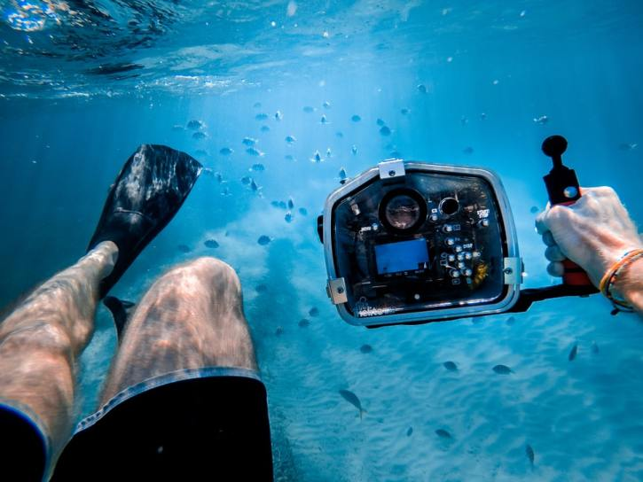 Swimmer taking photos of fish under water.