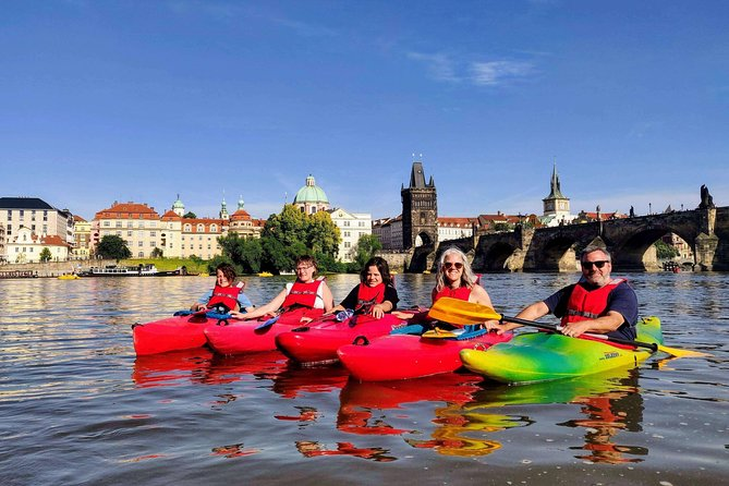 A group of tourists in kayaks on the river in Prague on a kayak tour.
