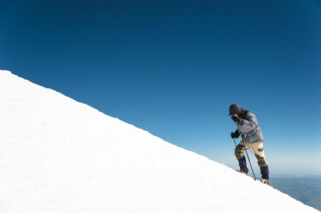 Marcheur qui gravit une montagne enneigée