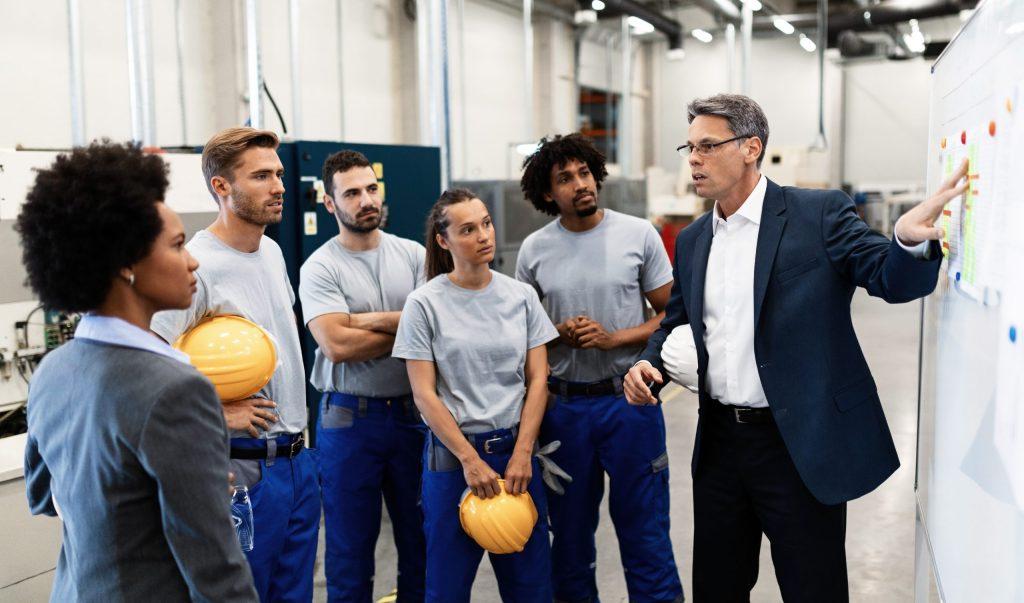 Semaine de la QVT 2020 groupe de salariés discutant autour d'un tableau blanc avec un responsable d''équipe