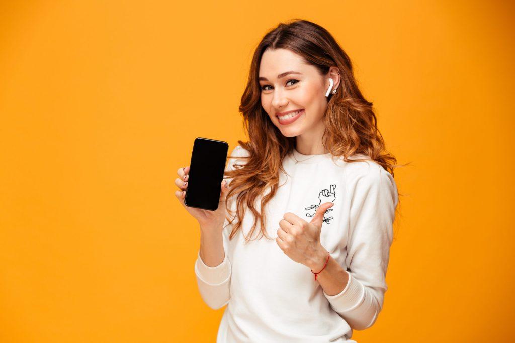 Semaine de la QVT 2020 Jeune femme souriante avec un téléphone en main et le pouce levé